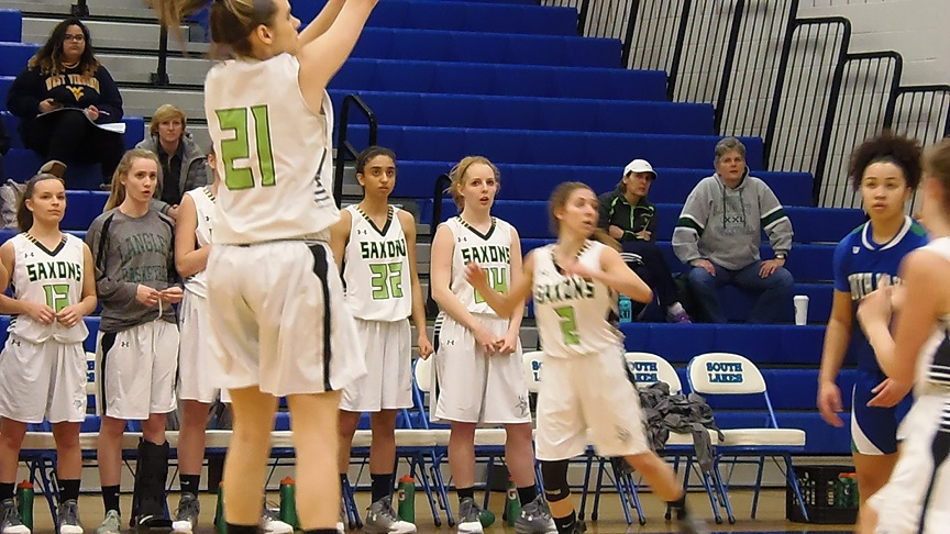 The Saxons' Emily Shively takes a jump shot as the Langley bench looks on.