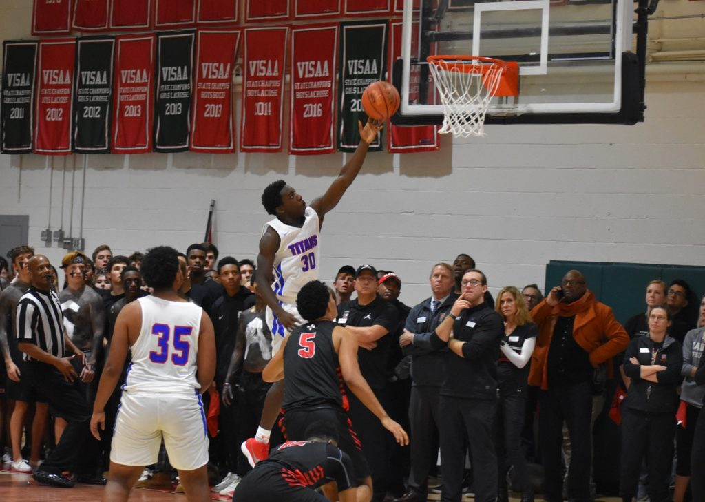 T.C. Williams' BJ Lee attacks the rim in the first half.