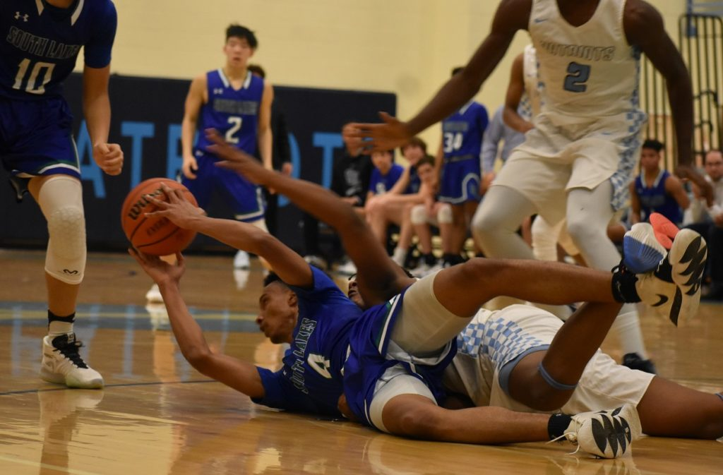 South Lakes' Kurtu dives and gets a loose ball on the floor, saving a possession for his team.