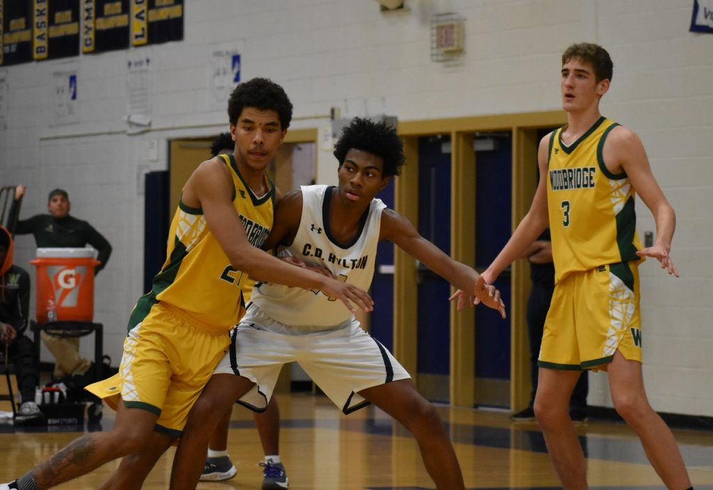 Jaden King (left) and Shane Feden give Hylton's Nate Arrington (19 points) some extra attention in the post.