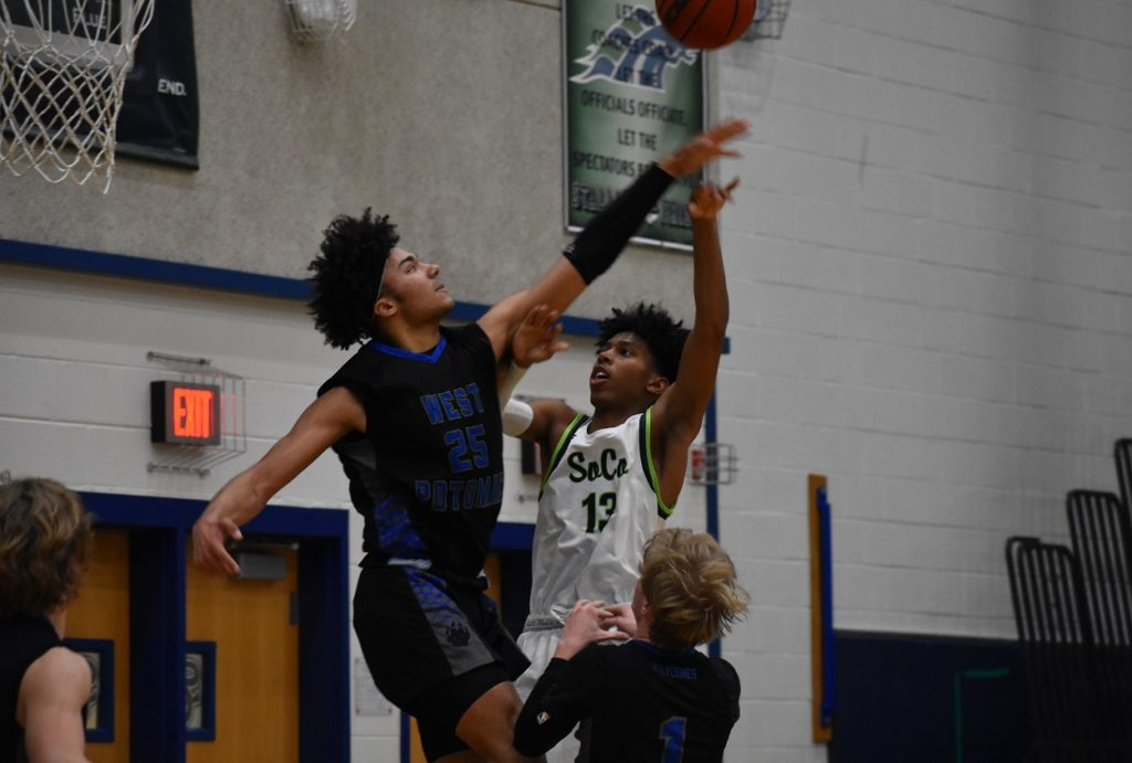 West Potomac kept it close early with tough defense. Here, Wolverines senior Colby Dessaure blocks a shot by Andre Speight.